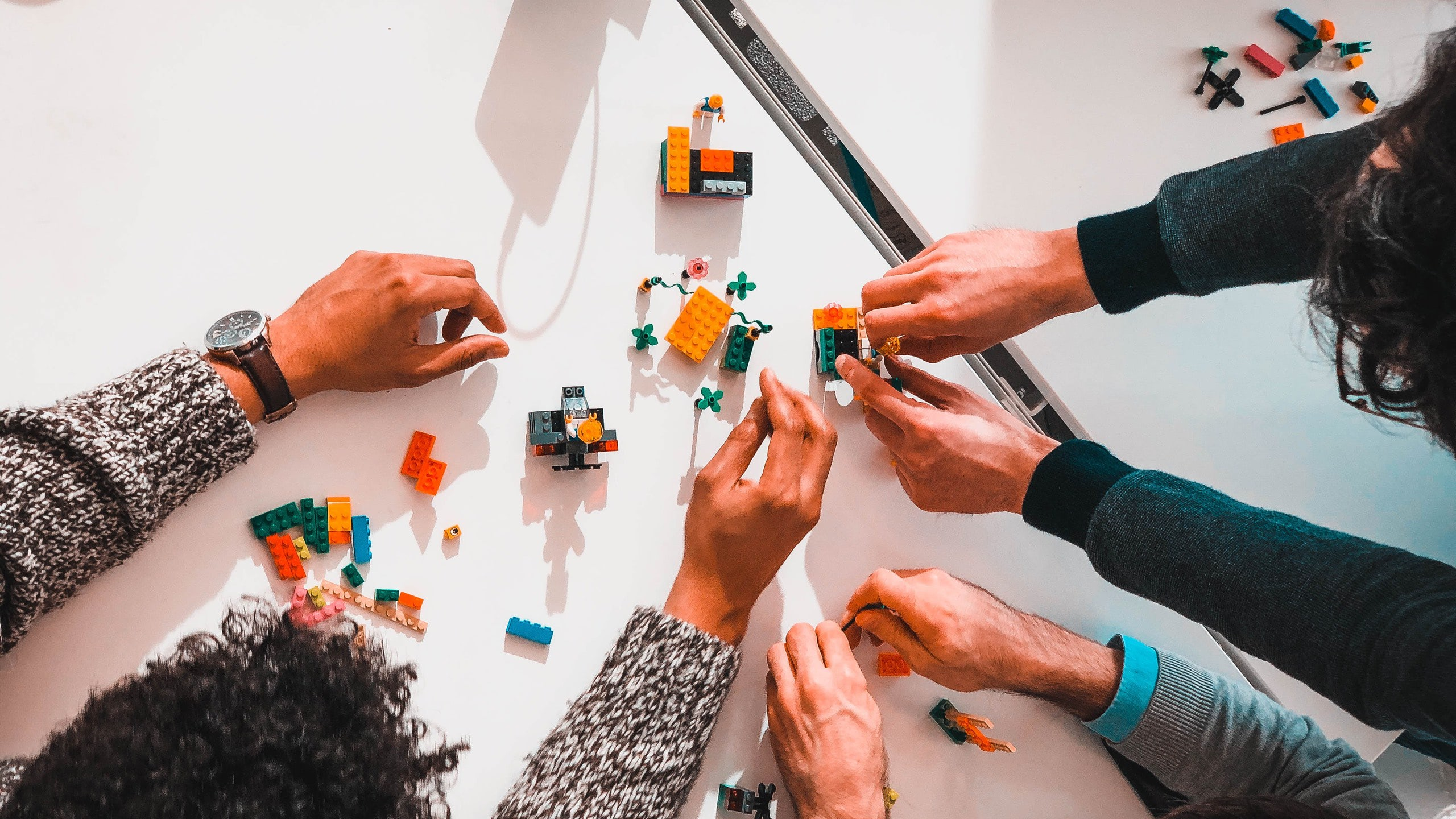 Overhead photo of a group of people assembling LEGO as part of a design thinking workshop