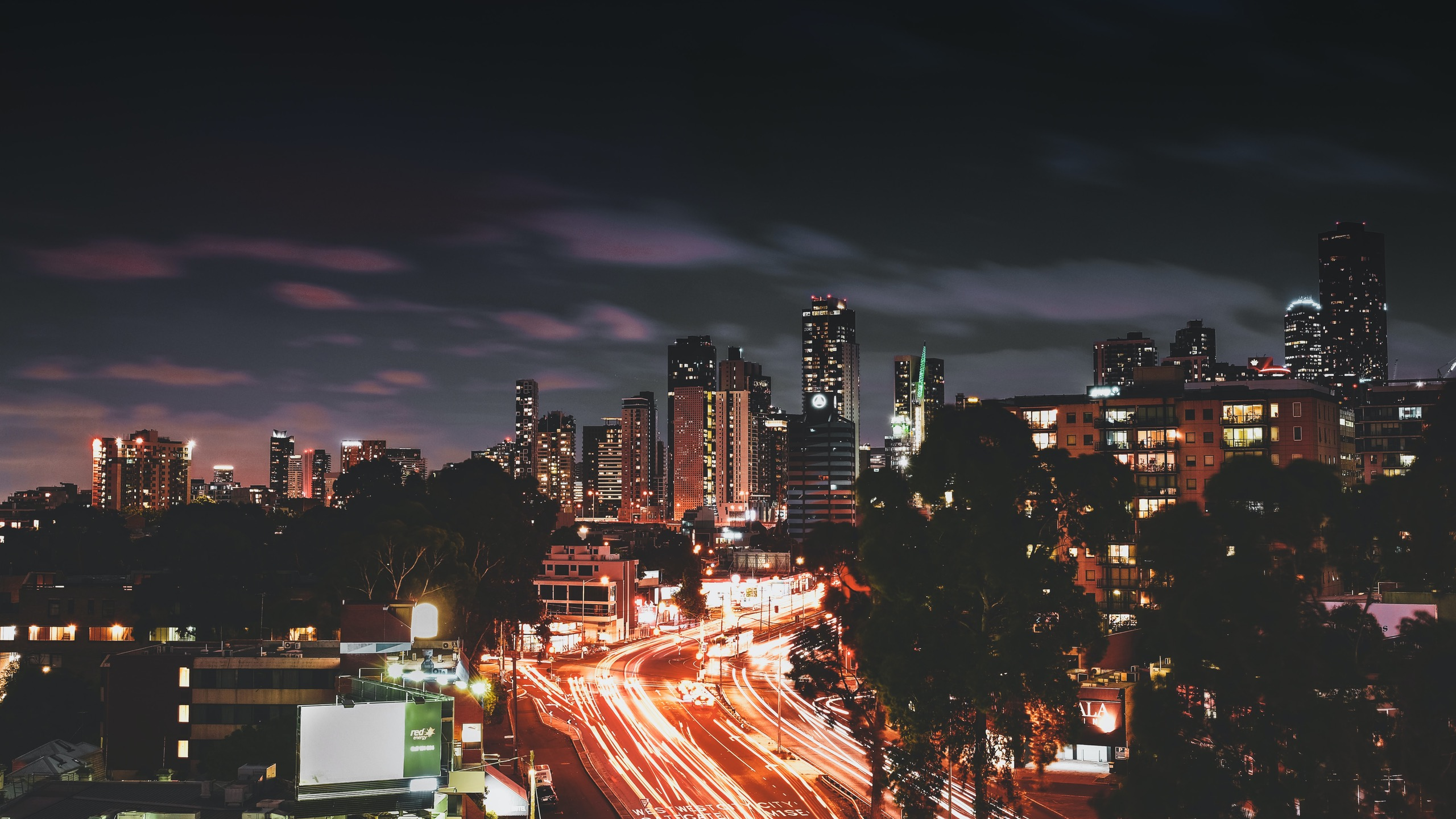 Long exposure photo at night of a freeway with the Melbourne cityscape in the background