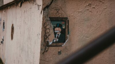 Cracked wall with a piece of art showing the monopoly man