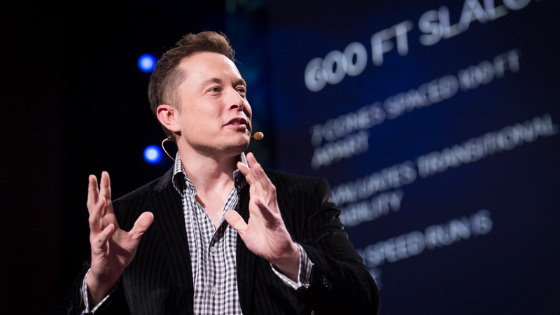 Elon Musk on stage, behind him is a large screen with blurred text.