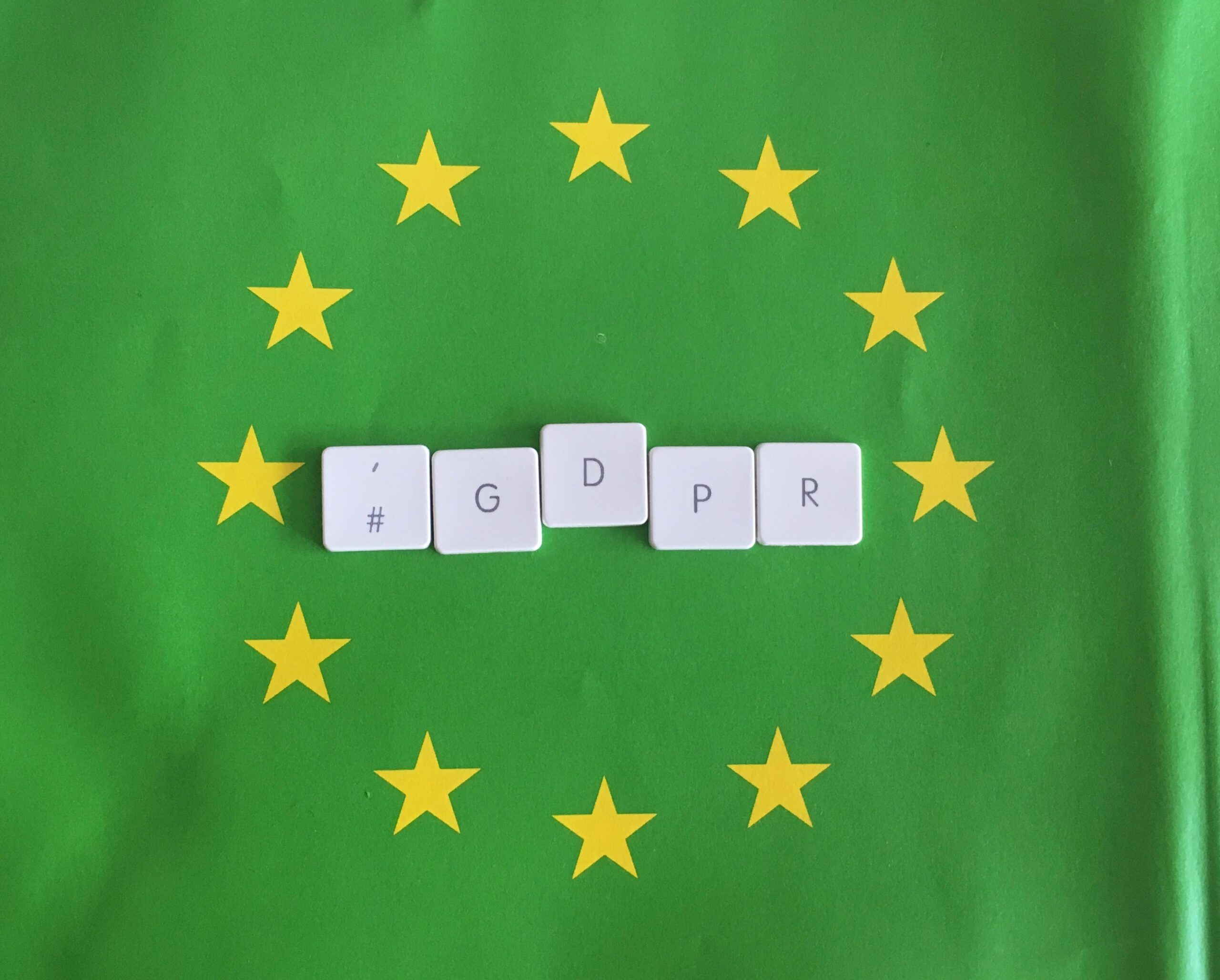 Green European Union flag with yellow stars and GDPR spelt out in keyboard letters