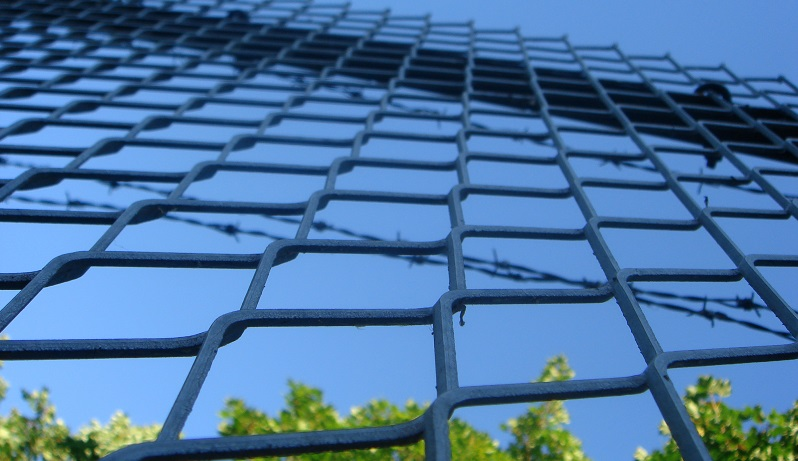 Image of barbed wire outside a prison (Image from Flickr: https://www.flickr.com/photos/dogbomb/641416098)