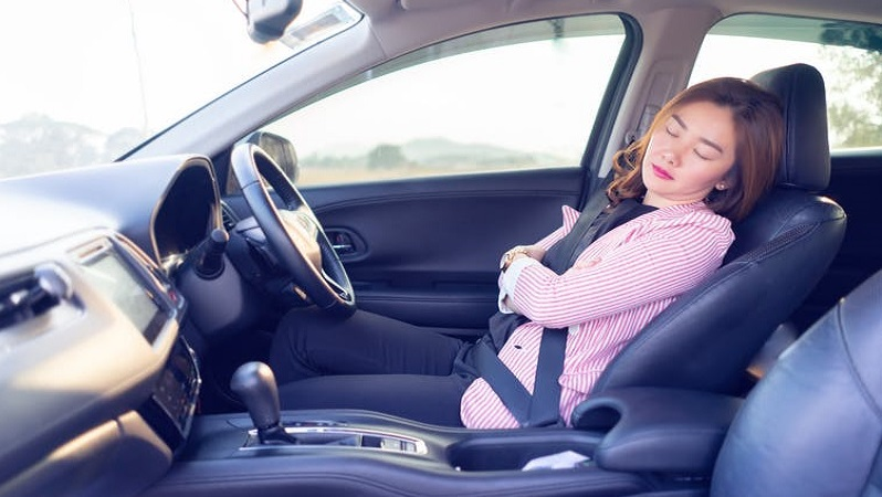 Image of a woman sleeping at the wheel of a car. (Shutterstock: https://www.shutterstock.com/image-photo/excessively-tired-young-asian-women-drivingsleeping-1116595130?src=KoX4o3D8SPyojngBQDLtiA-1-3)