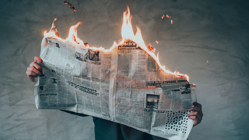 person holding a newspaper that is on fire