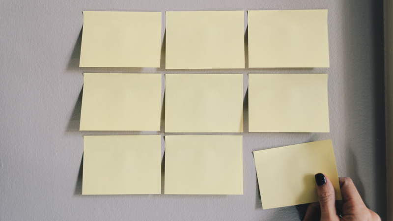 Blank Post-It notes affixed to a wall. A hand is taking one of them off