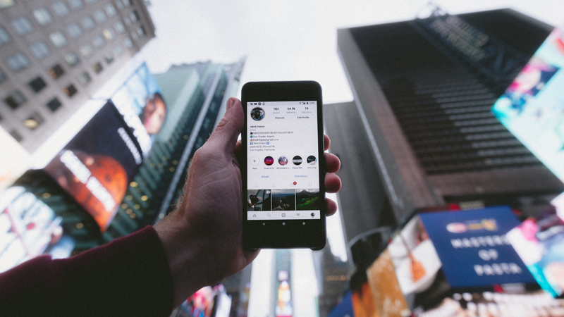 Photo of a phone with buildings in the background. The phone has an influencer's instagram account open`