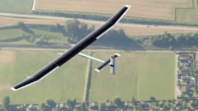 Aerial photo of a solar powered plane flying over fields.