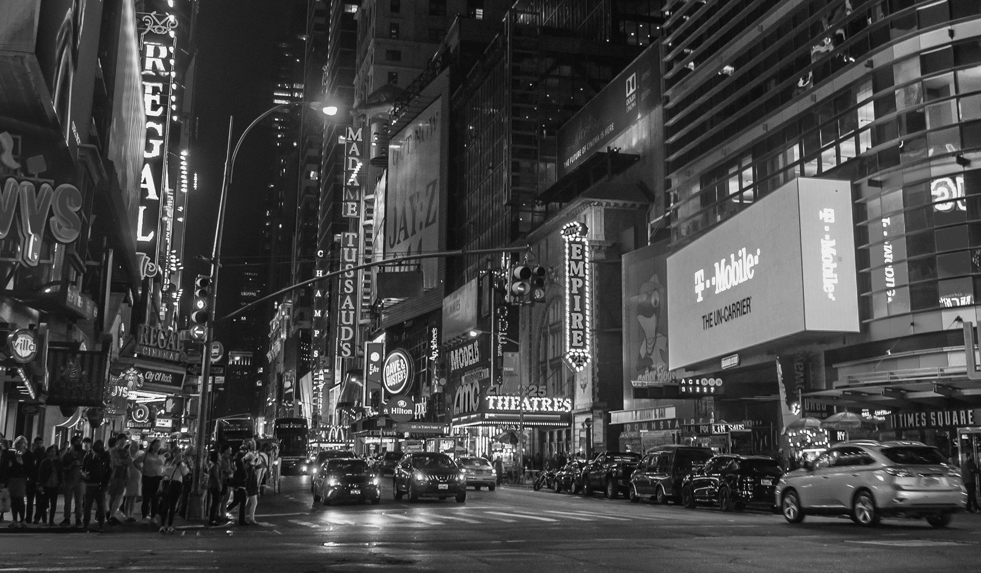 Black and white photo of a busy city intersection surrounded by billboards