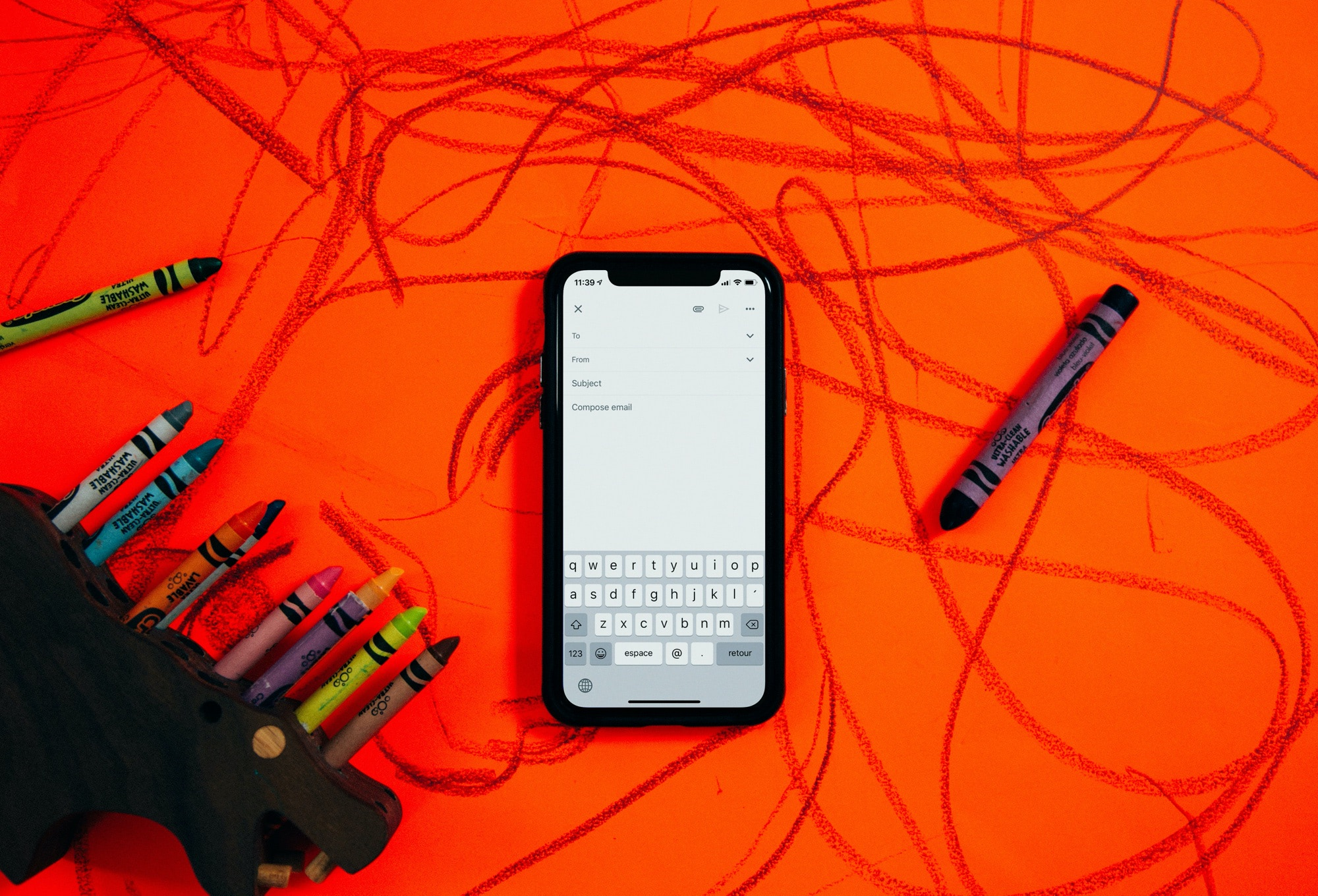 Phone showing an email app resting on a red table covered in crayon drawings