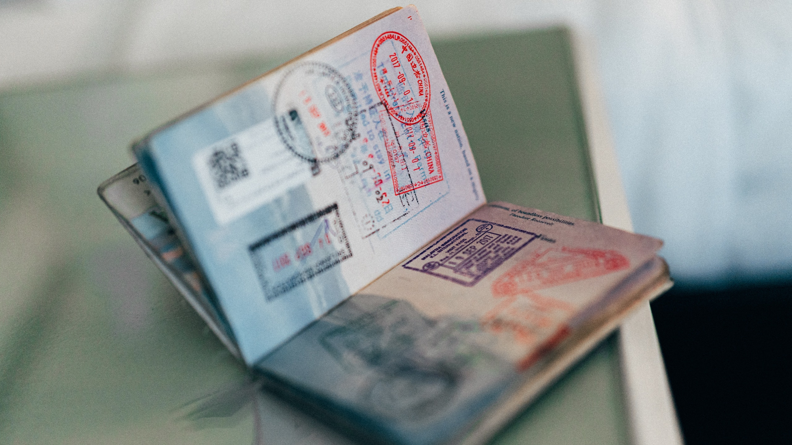 Open passport covered in immigration stampson a table