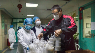 People in protective clothing packaging meals