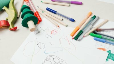 Pens and toys on a table, a child's drawing on paper
