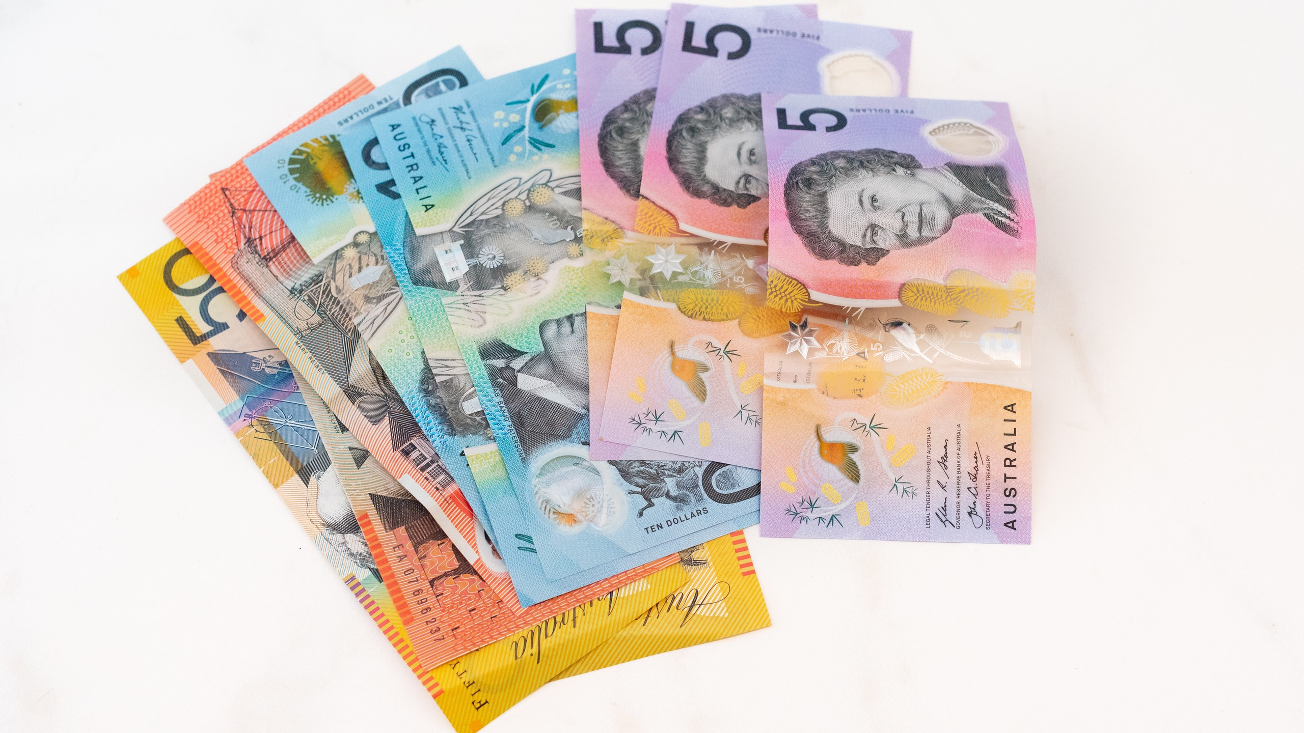 Assortment of Australian bank notes on a white table