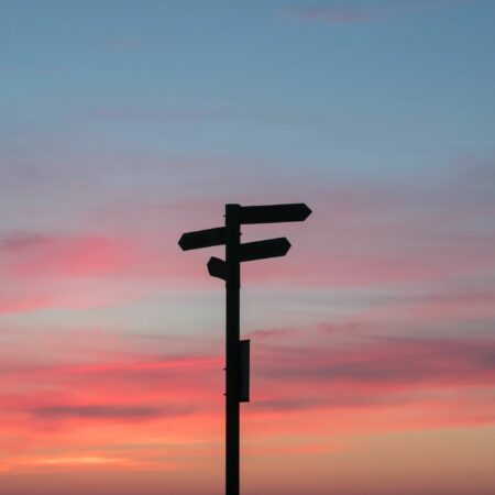 sunset with the silhouette of a road sign