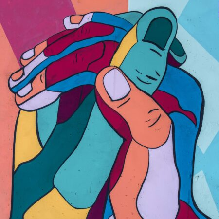 artwork of two multicoloured hands holding each other