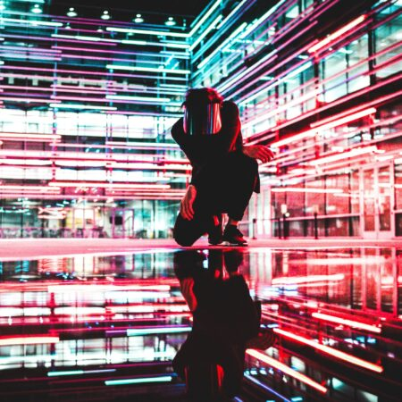 person knealing in a courtyard at night surrounded by neon lights