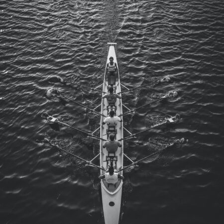 overhead black and white photo of a rowing team in the water