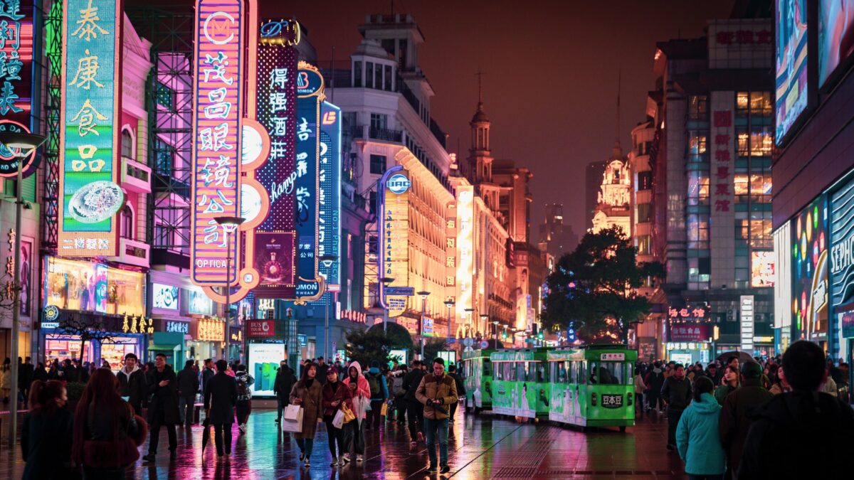 Chinese city street at night showing large neon signs